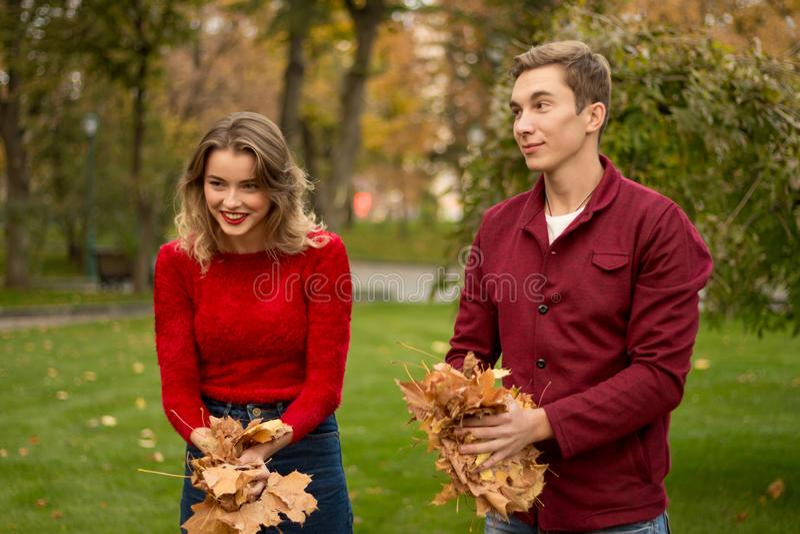 Um par joga acima as folhas amarelas, bordo, acima, enganando ao redor, outono data Rindo e tendo o divertimento foto de stock royalty free