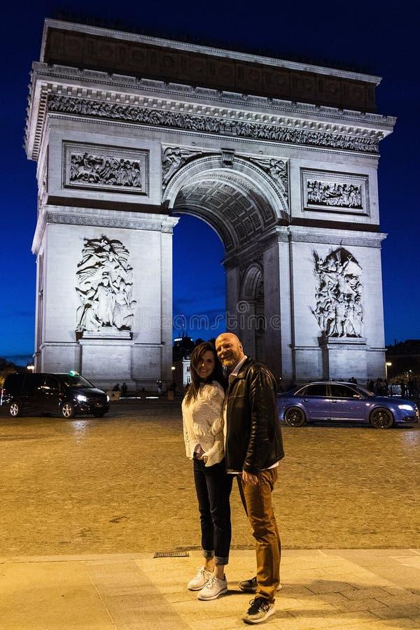 Um par levanta fora de Arc de Triomphe em Paris, França foto de stock royalty free
