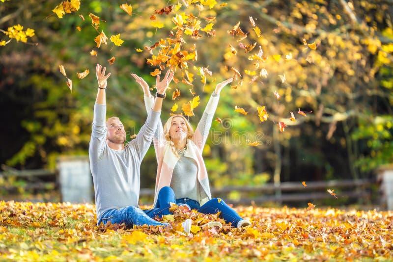 Um par loving em um parque do outono encontra-se nas folhas fotografia de stock royalty free