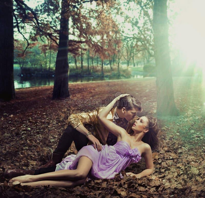 Um par loving que encontra-se nas folhas de outono imagens de stock