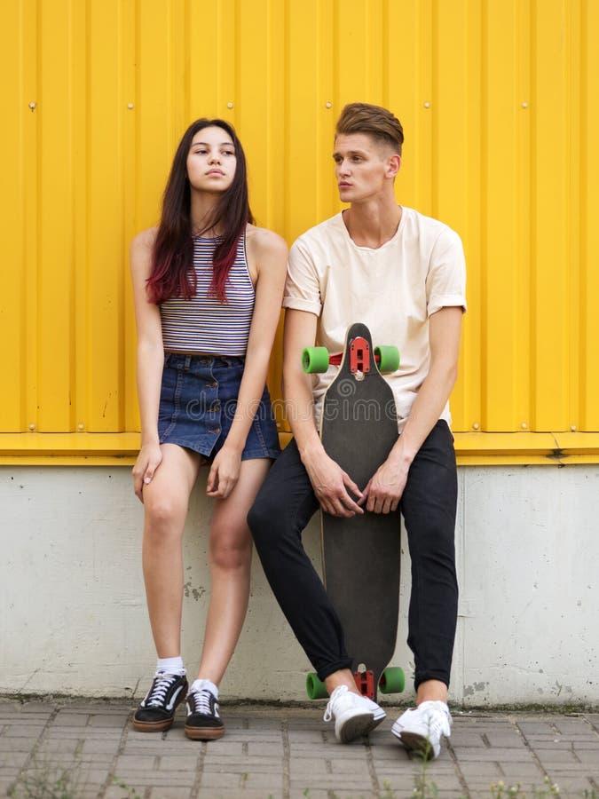 Um par um menino e uma menina da adolescência com um longboard em um fundo amarelo Conceito do abrandamento e da atividade imagem de stock