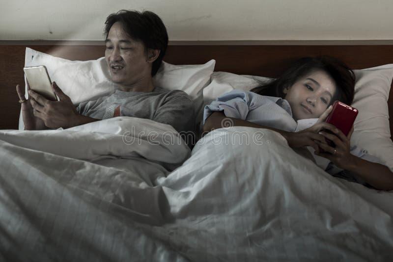 Um par na cama que está interessado em seus telefones celulares Não mim fotos de stock royalty free
