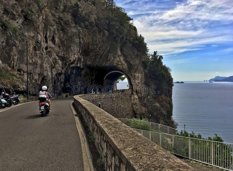 Um par no velomotor que viaja ao longo da movimentação cênico da costa de Amalfi foto de stock royalty free