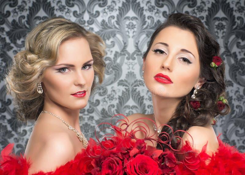 Um par noivas novas e atrativas em penas vermelhas fotografia de stock