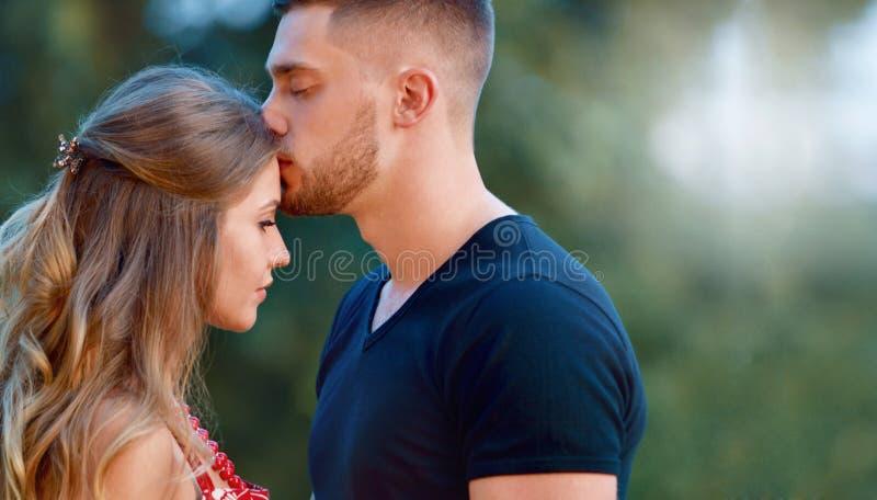 Um par nos homens novos bonitos do amor que beijam em um verão estaciona em um dia ensolarado foto de stock royalty free