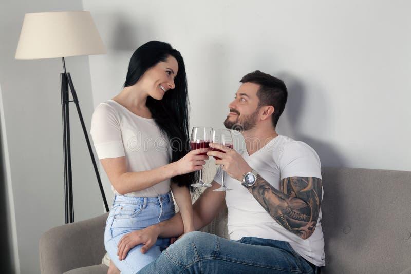Um par novo bonito que senta-se no sofá e no vinho bebendo, estão felizes junto foto de stock royalty free