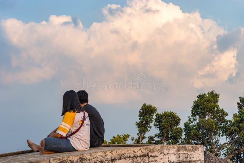 Um par novo de adolescentes tailandeses locais na natureza que senta-se em uma pedra contra o céu imagem de stock