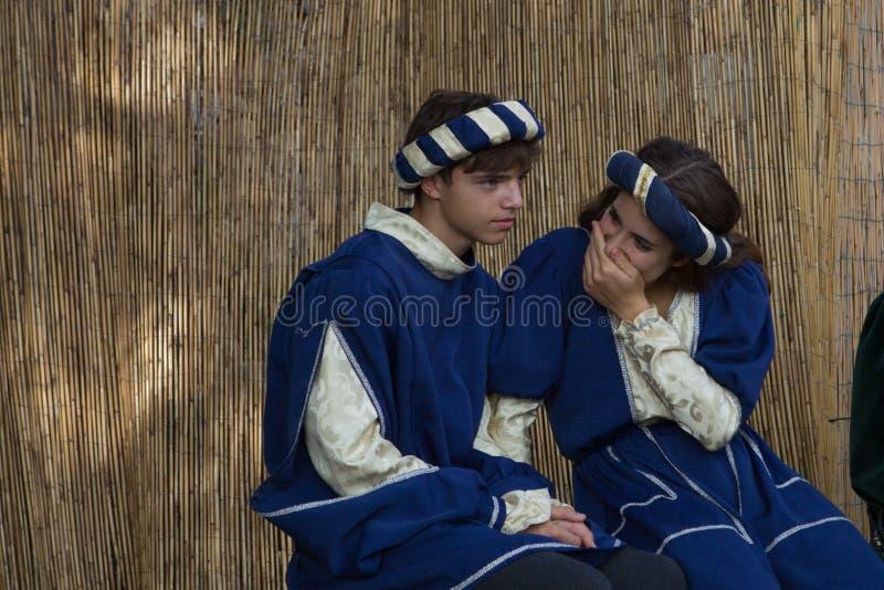 Um par novo de cortesões que têm o divertimento durante um banquete medieval imagem de stock