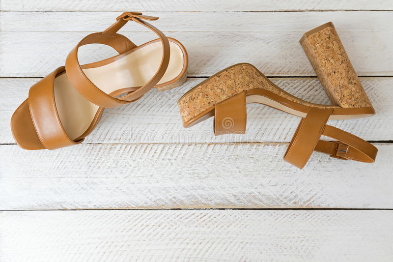 Um par novo de saltos altos marrons à moda com solas da cortiça, beautifu fotografia de stock