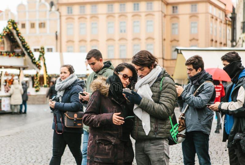 Um par novo de turistas olha um mapa em um telefone celular imagem de stock