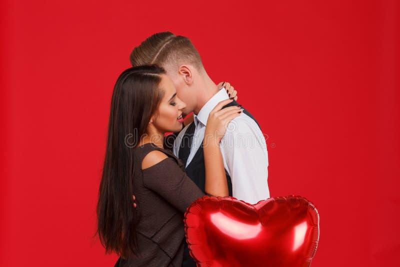 Um par novo e bonito que beija em um fundo vermelho O conceito do dia do ` s do Valentim imagens de stock