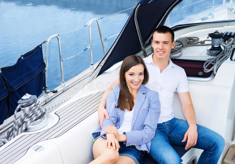 Um par novo e feliz que relaxa em um barco foto de stock