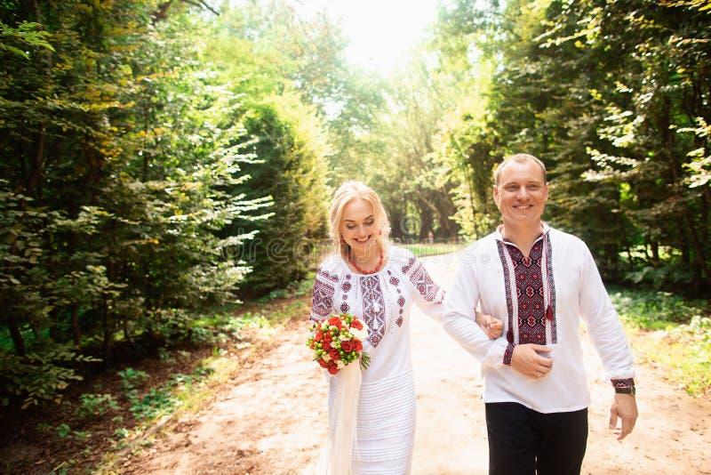 Um par novo em um ramalhete ucraniano tradicional do whith da roupa que anda no parque ensolarado fotos de stock royalty free