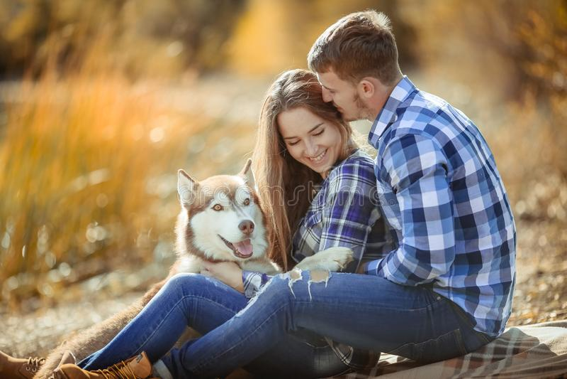 Um par novo está sentando-se pelo lago no por do sol com um cão ronco da raça imagem de stock royalty free