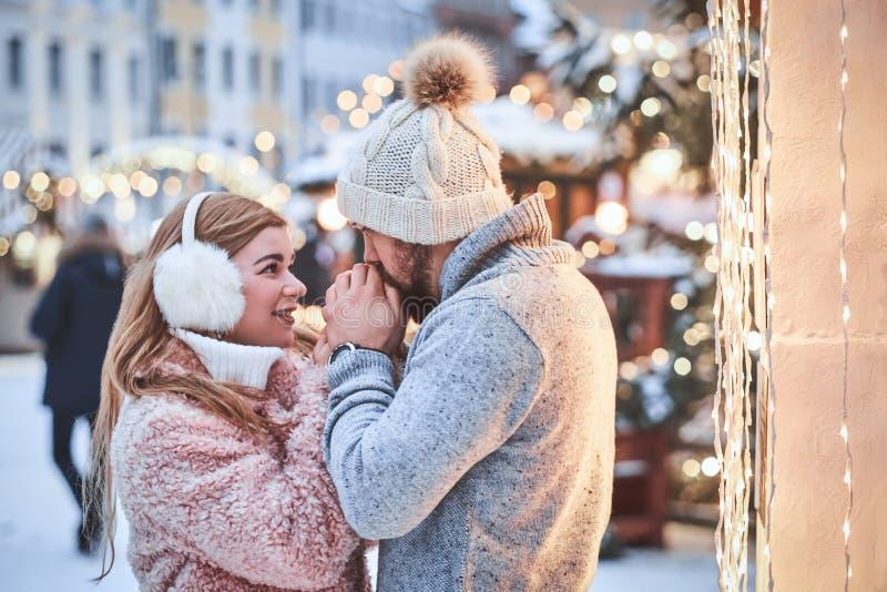 Um par novo feliz no amor, mãos de aquecimento do homem sua amiga que aprecia passando o tempo junto perto de um Natal da cidade foto de stock royalty free