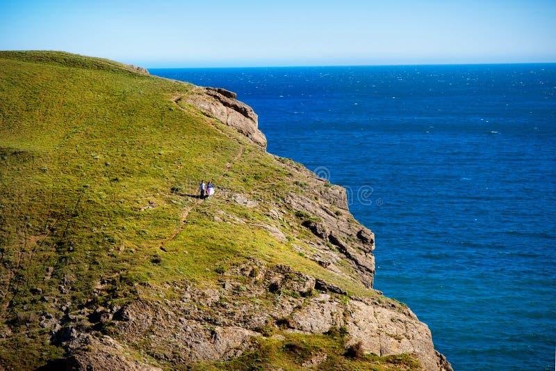 Um par novo loving no fundo de uma paisagem bonita - mar e montanha imagem de stock royalty free