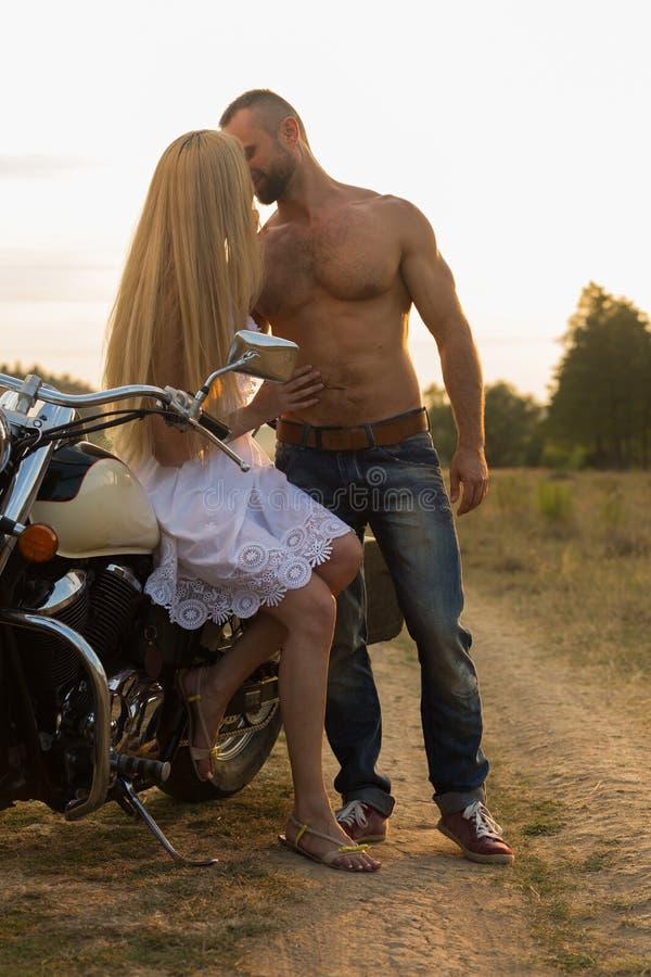 Um par novo no amor em uma motocicleta no campo fotos de stock royalty free