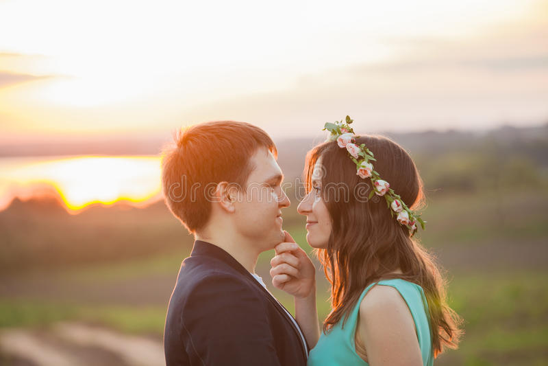 Um par novo no amor exterior no por do sol fotografia de stock