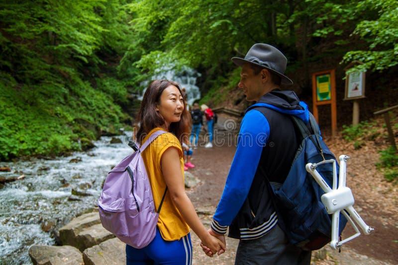 Um par novo que cruza uma montanha flui ao para fora andar junto Os viajantes estão perto das cachoeiras imagens de stock