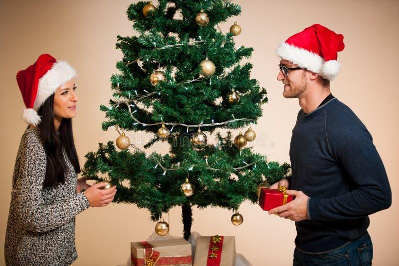 Um par novo que está na frente da árvore de Natal e do givin fotografia de stock royalty free