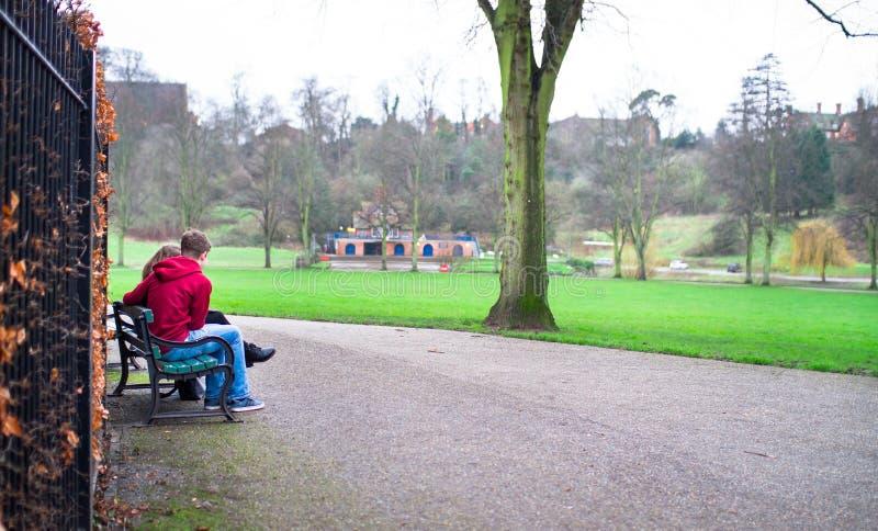 Um par novo senta-se em um banco de parque em Inglaterra imagens de stock royalty free