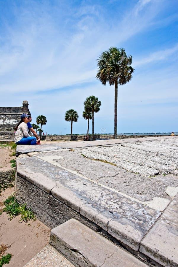Um par olha senta-se em uma terraplenagem em Castillo De San Marcos ao olhar sobre ao rio de Mantazas imagens de stock royalty free