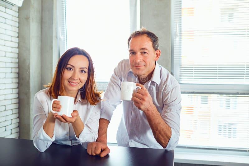 Um par povos de meia idade com as canecas em suas mãos dentro fotos de stock royalty free