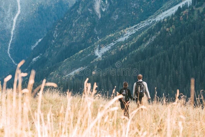 Um par que anda em um prado na frente de uma paisagem montanhosa fotos de stock royalty free
