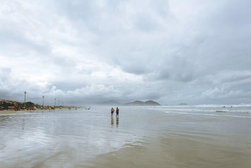 Um par que anda na praia fotografia de stock