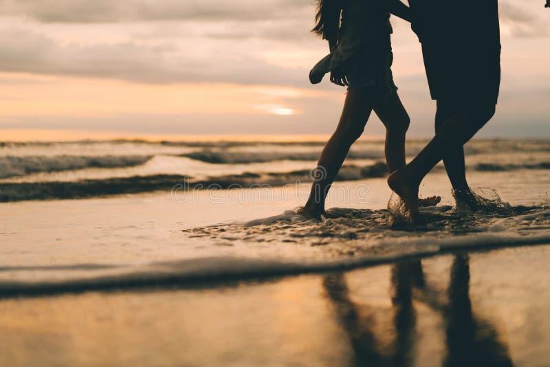 Um par que anda perto do por do sol de observação do oceano imagem de stock royalty free