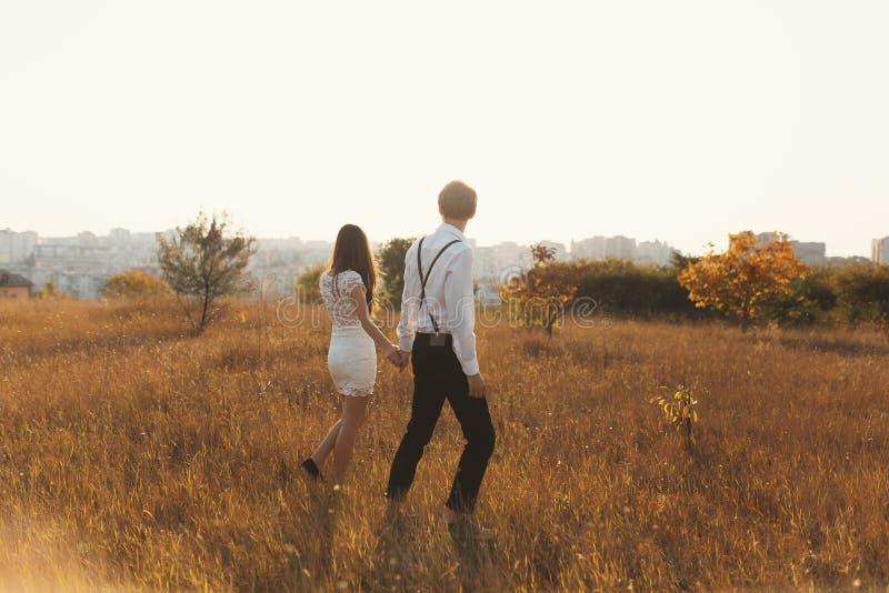 Um par que aprecia uma caminhada, guardando as mãos, com a cidade no ho imagem de stock royalty free