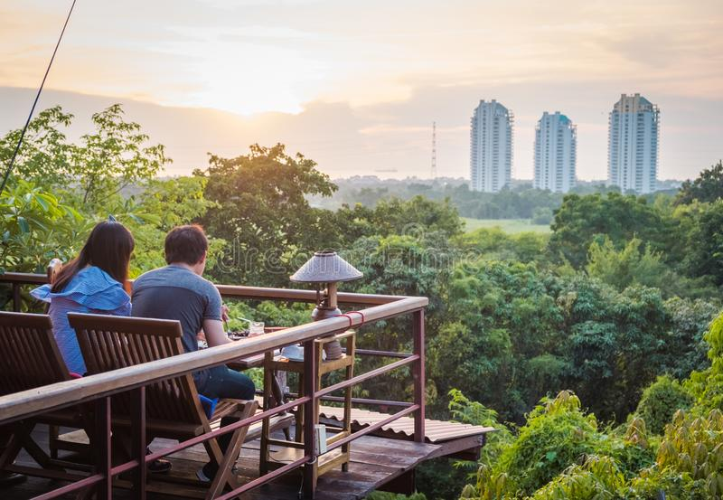 Um par que dinning na frente da floresta e das construções fotografia de stock