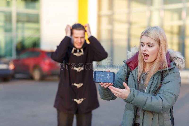 Um par que está na rua, a menina está guardando um smartphone quebrado, e o indivíduo é estando e guardando a cabeça fotografia de stock royalty free
