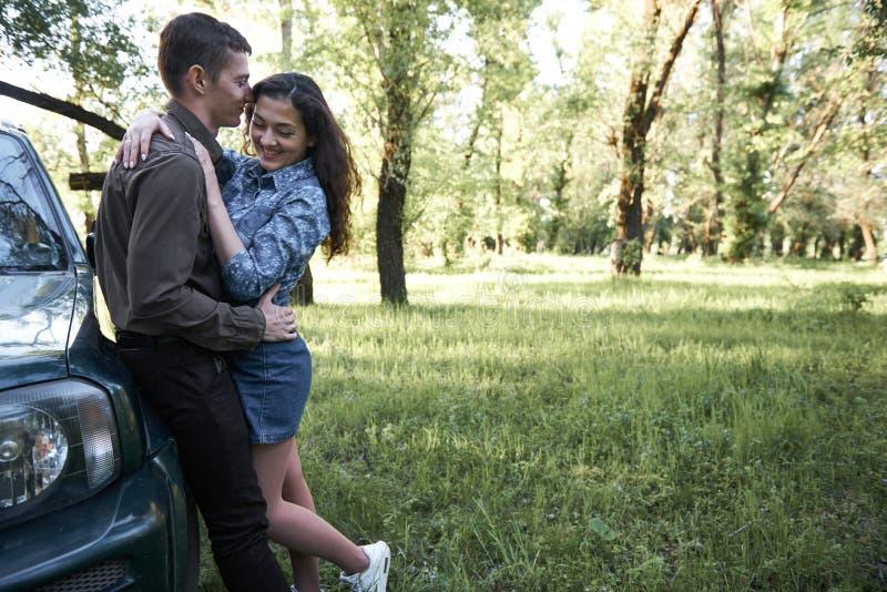 Um par que está perto do carro na floresta, nos sentimentos românticos e no amor imagens de stock