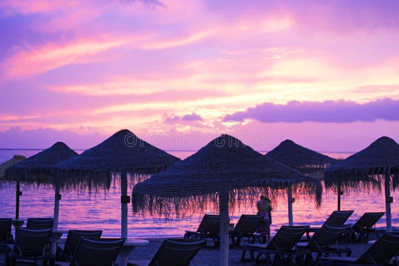 Um par que olha um por do sol bonito na praia fotografia de stock royalty free