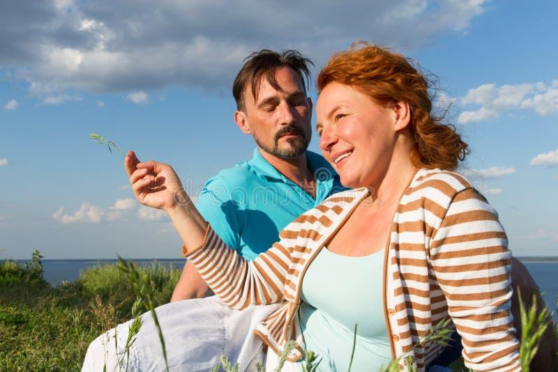 Um par que relaxa na grama verde e no céu azul Acople o encontro na grama exterior com fundo da água e do céu fotos de stock