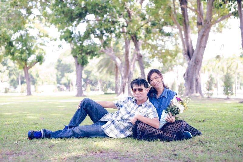 Um par que relaxa no verde imagem de stock