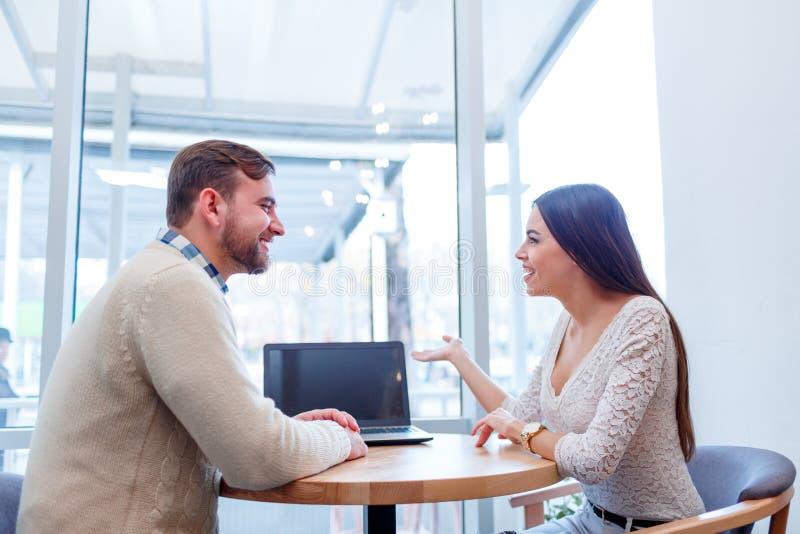 Um par que senta-se em um café, comunicando-se e sorrindo docemente fotos de stock