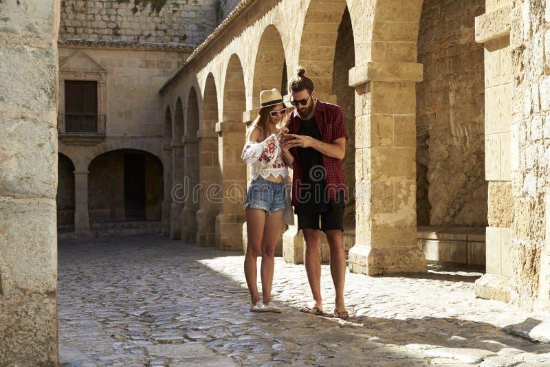 Um par que sightseeing em Ibiza usando um telefone para a orientação fotografia de stock royalty free