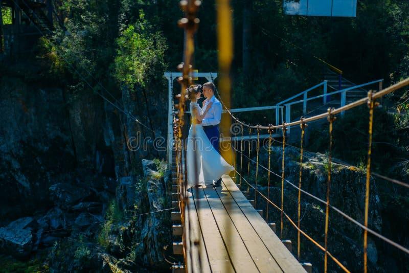 Um par recém-casados estão na ponte de suspensão e no olhar em se No fundo, na natureza selvagem e nas rochas imagens de stock royalty free