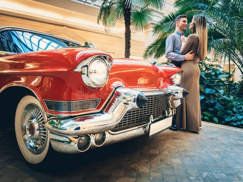 Um par romântico está estando pelo carro vermelho Um homem está abraçando uma mulher Clássicos americanos O indivíduo e a menina  imagens de stock royalty free