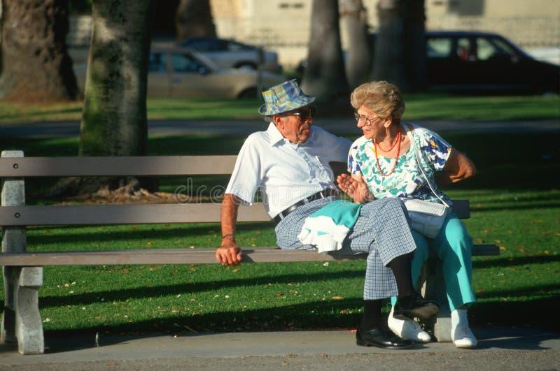 Um par sênior que senta-se em um banco de parque fotos de stock
