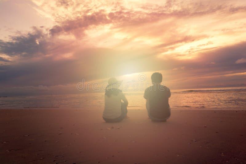 Um par senta-se no Sandy Beach foto de stock royalty free