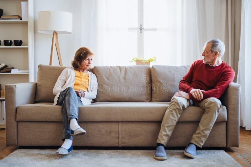 Um par superior que senta-se em um sofá em casa, tendo um argumento imagens de stock royalty free