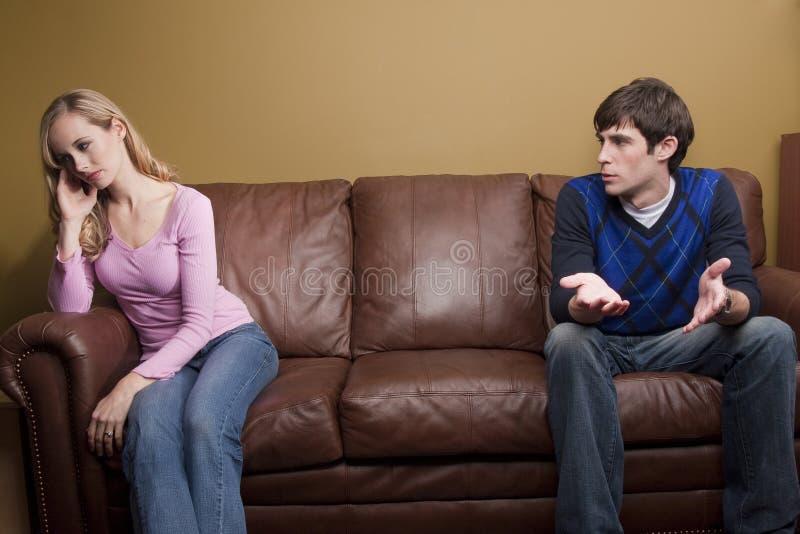 Um par tem um argumento no sofá imagem de stock royalty free