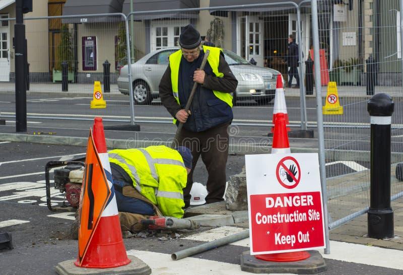 Um par trabalhadores realizam reparos essenciais da manutenção na tomada da compra do retalho da vila do ` s Kildare da Irlanda n imagem de stock