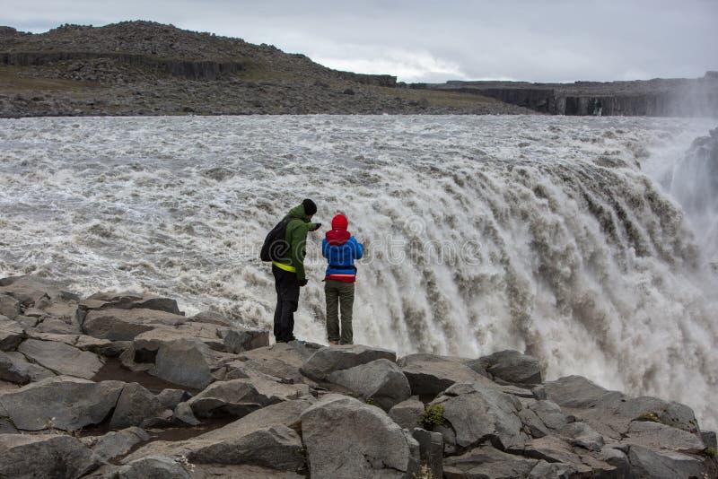Um par turistas estão na borda mesma da cachoeira poderosa Dettifos imagens de stock