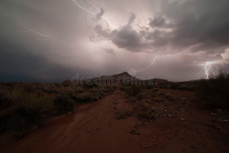 Um parafuso de curto circuitos na distância quando uns outros ziguezagues através do céu que ilumina o deserto abaixo do Mesa da  imagem de stock royalty free