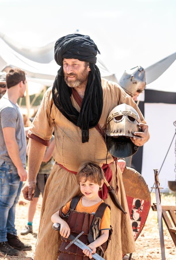 Um participante do festival do cavaleiro levanta com um visitante pequeno vestido na armadura no parque de Goren em Israel foto de stock