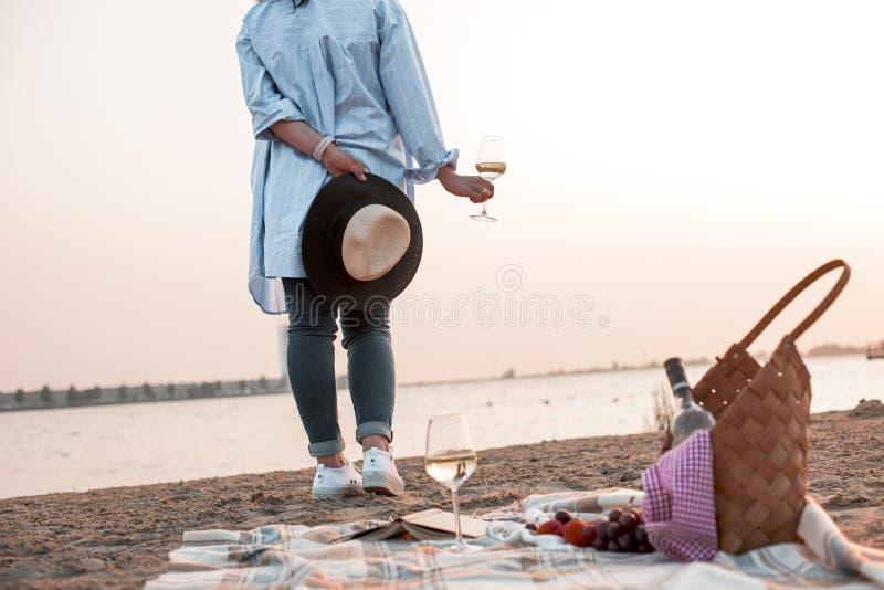 Um partido na praia no por do sol e em uma menina com um vidro do vinho Noite romântica no verão pelo mar Piquenique Copie o espa imagens de stock royalty free